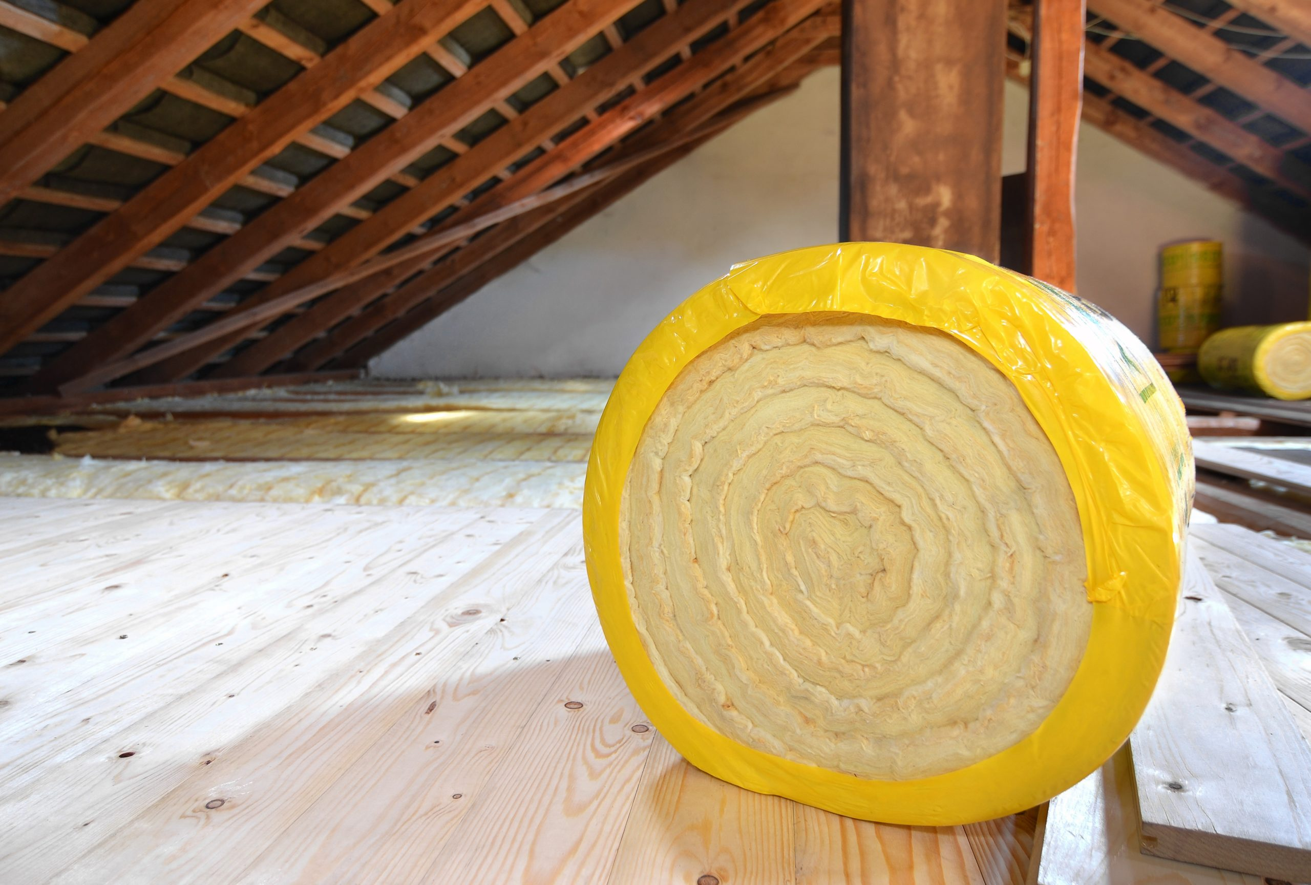 A roll of fiberglass batt insulation on an attic floor
