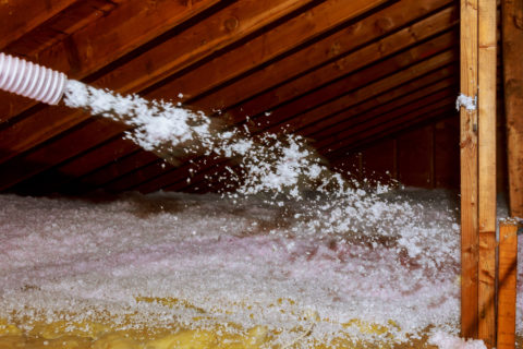 Worker spraying loose fill insulation in house attic